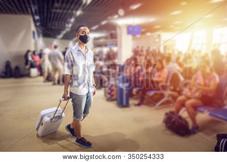 Asian Tourist With Luggage ,wearing Mask To Prevent During Travel Time At The Airport Terminal For P