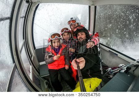 Family Riding Cabin Cable Car On Winter Vacation Skiing.