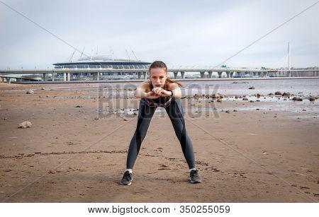 1 White Slender European Girl Doing Warm-up, Doing Leans Forward On The Beach Against The Background