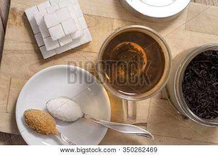Different Types Of Sugar Lie On A Wooden Board. Tea Brewed In A Glass.