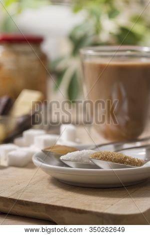 Honey, White Sugar, Cane Sugar In The Foreground Enlarged. In The Background, Sugar Cubes Lie On A W