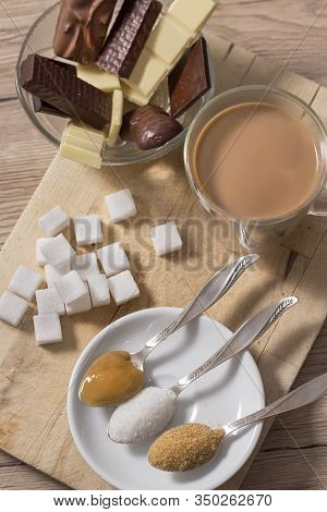 Different Types Of Sugars And Sweets Lie On A Wooden Counter. Honey, Loose White Sugar And Cane Suga
