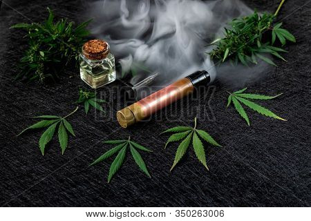Cannabis Liquid. Vape Cbd Or Thc, Vaping Marijuana And Hemp. Against A Dark Background. Thick Steam.