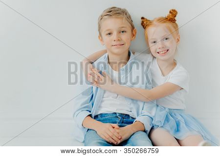 Friendly Small Girl And Boy Hug And Sit On Floor Against White Background, Have Positive Expressions