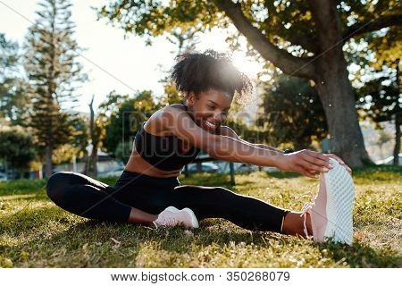 Smiling Portrait Of An Sporty Fit African American Young Woman Sitting On Lawn Stretching Her Legs I