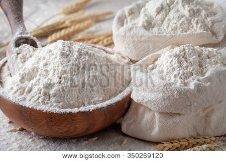 Wheat Flour In Wooden Bowl And Burlap Bag On Kitchen Table. Ingredient For Baking.