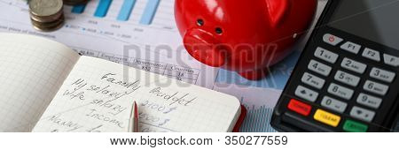 Close-up Of Red Piggy Bank Terminal And Notebook With Notations. Monthly Expenses On Rent Car Food A