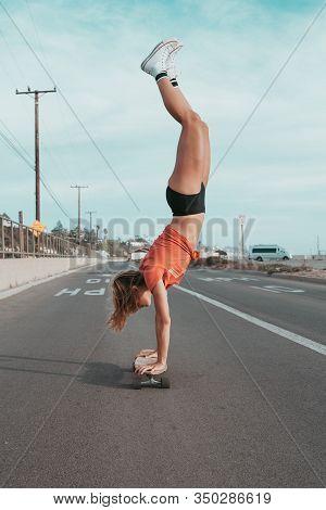 Skater Girl Making A Handsand On Her Skateboard In Malibu