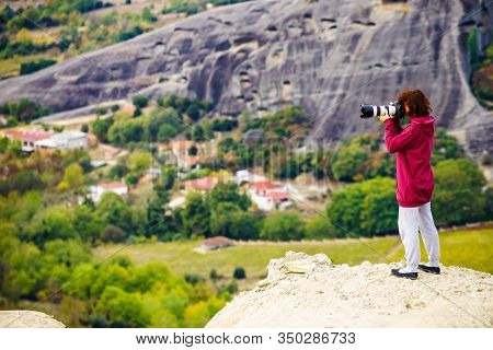 Woman Tourist With Professional Camera Taking Picture Film Video From Monastery. The Meteora Monaste