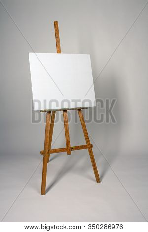 Blank Canvas On Easel. Clean Cloth Stretched On Subframe With Copy Space. Tripod For New Oil Paintin