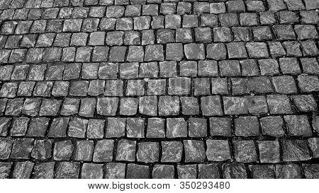Granite Cobblestone Sidewalk Cubic Stone Close Up Background Texture. Street Pavement Texture. Black