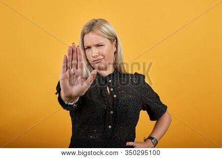 Young Blonde Girl In Black Dress On Yellow Background An Irritated Woman Shows Off Her Hands Which S