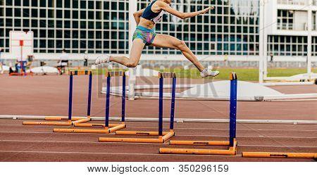 Young Female Athlete Run 400 Meters Hurdles In Athletics