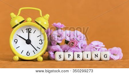 Spring Forward, Springtime, Daylight Savings Time Concept, Yellow Alarm Clock And Flowers On Orange