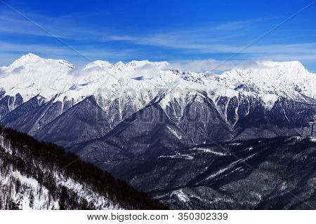Winter Mountains And Blue Sky With Beautiful Clouds And Their Shadows Fall On Peaks Of Caucasus Moun