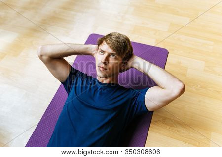 Top View Of Handsome Athletic Caucasian Young Man Slim Body Exercising Doing Sit Up Exercise On Yoga