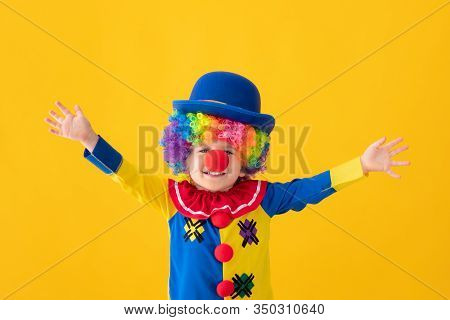 Funny Kid Clown Playing Against Yellow Background