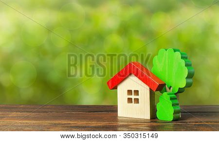Wooden House And Trees. Affordable Comfortable Housing. Purchase Of Apartments And Real Estate, Rent