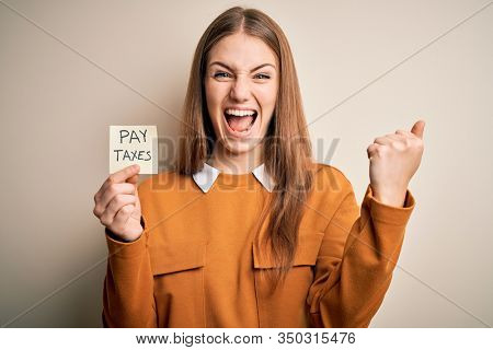 Young beautiful blonde woman holding pay taxes to goverment reminder over yellow background screaming proud and celebrating victory and success very excited, cheering emotion