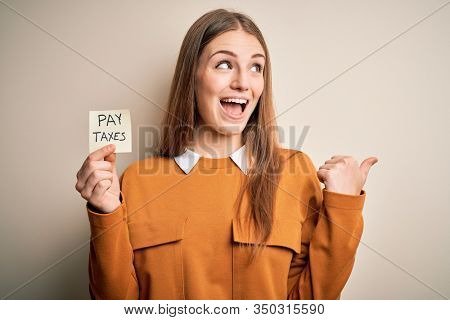 Young beautiful blonde woman holding pay taxes to goverment reminder over yellow background pointing and showing with thumb up to the side with happy face smiling