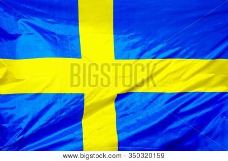 Fabric Texture Flag Of Sweden. Flag Of Sweden Waving In The Wind. Sweden Flag Is Depicted On A Sport