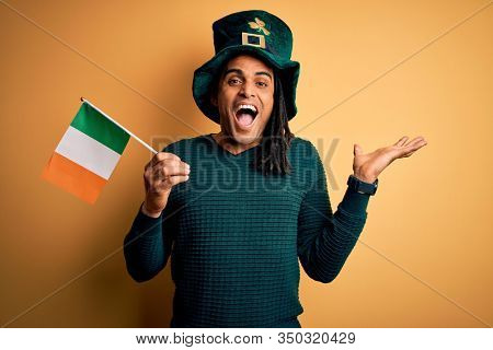 African american man wearing green hat holding irish ireland flag celebrating saint patricks day very happy and excited, winner expression celebrating victory screaming with big smile and raised hands