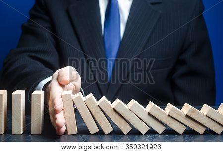 Businessman Stops Domino Falling. Strategy Development. Debt Restructuring. Risk Management Concept.