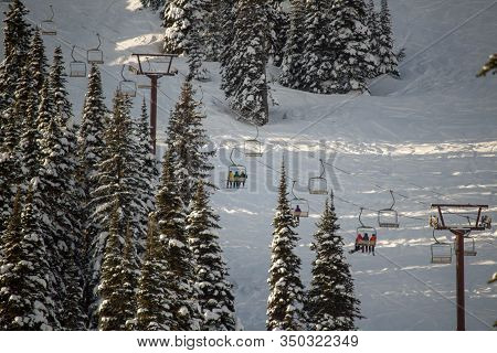 Snowboarders And Skiers Riding A Chairlift In The Momring