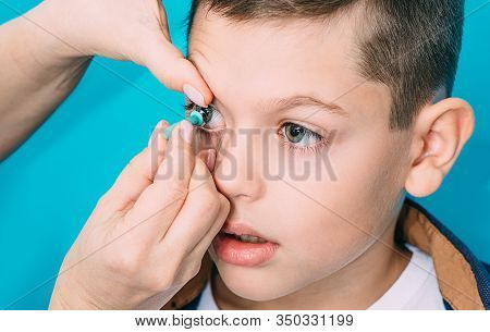 Contact Lenses For Vision Correction In Children. Ophthalmologist Putting On Contact Lens To A Teena