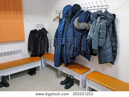 Jackets And Winter Outerwear Hanging On Hooks On The Wall. Jackets, Fur Coats And Coats Hang In The
