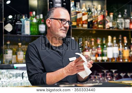 Elderly Bartender Cleans The Glass. A Handsome Bartender Polishes A Glass Of Wine Glasses. The Conce