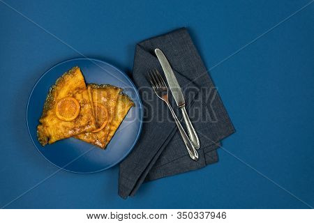 Two Crepe Suzette Pancakes Golden Toasted With Slices Of Orange And In Syrup On A Plate With Cutlery