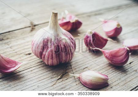 Rustic Style Garlic On Vintage Wooden Background. Fresh Young Peeled Purple Garlic.