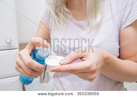 Woman Wetting A Cotton Pad With A Micellar Make Up Remover, Cleansing And Purifying Face Skin.