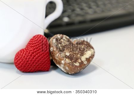 Valentine Day In Office, Cup Of Coffee, Red Knitted Heart And Gingerbread On Background Of Computer
