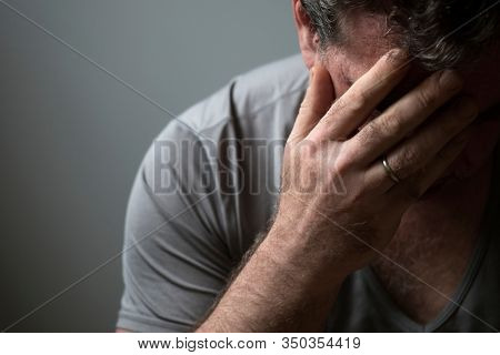 Unhappy sad man in depression covered his face with his hand