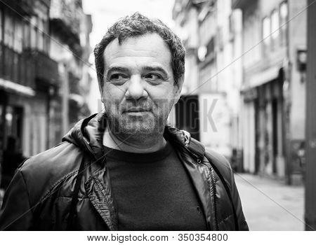 Happy smiling adult man on a city street black and white portrait. Real people everyday life