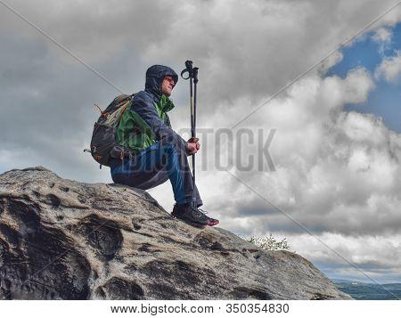 Tired Man Hiker Enjoy The View At Mountain Peak Cliff. Man Sit On Sandstone Peak.