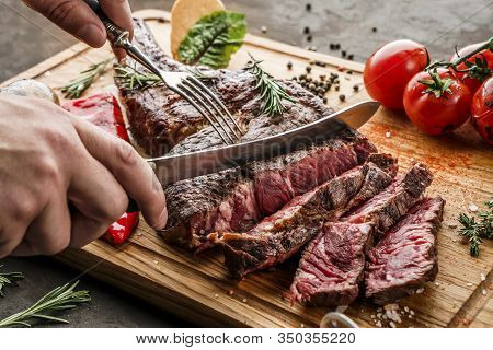 Hands Cut Grilled Tomahawk Meat Medium Rare Or Rib Eye Steak On Wooden Cutting Board With Grilled Ve