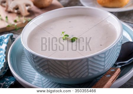A Bowl Of Delicious Cream Of Mushroom Soup With Thyme Garnish.