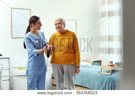 Care Worker Helping Elderly Woman To Walk In Geriatric Hospice