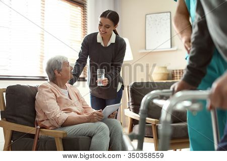 Care Worker Giving Water To Elderly Woman With Tablet In Geriatric Hospice