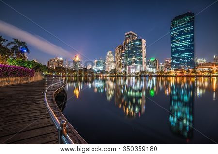 Skyscrapers And Lake With Wooden Walk Way In City Park. View Of Benjakiti Park At Night. Beautiful N