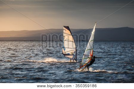 Windsurfer Surfing The Wind On Waves In Neusiedl Lake In Austria At Sunset. Recreational Water Sport