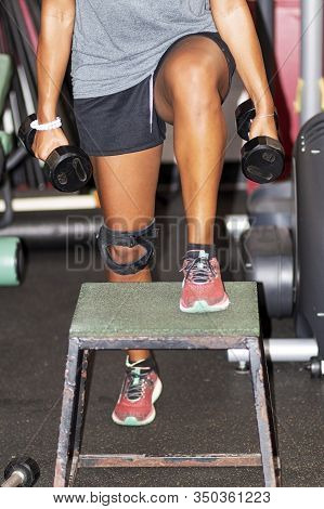 An African American Girl Is Stepping Up On A Plyo Box While Holding Dumbells In Her Hands Inside A G