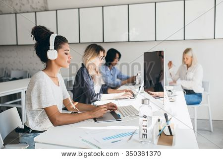 Concentrated African Female Web-designer Using Graphics Tablet While Her Colleagues Writing Reports.