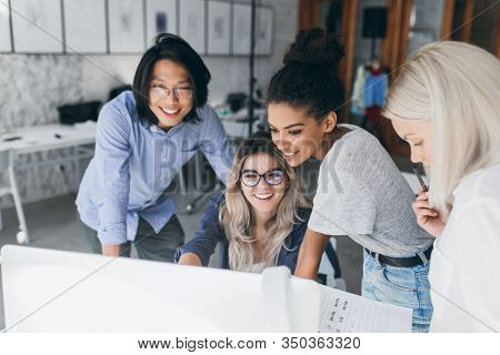 Long-haired Blonde Secretary In Glasses Laughing While Looking At Computer With Asian Programmer And
