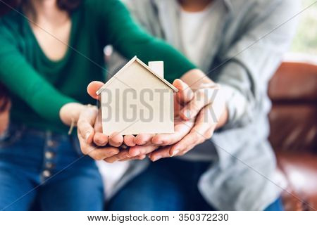 Couple Hands Holding Housing Model For Future Real Estate Saving, People Hand Joint To Protection Ho