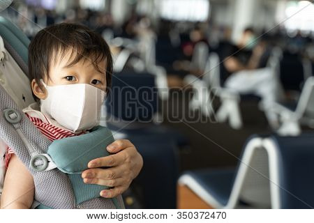 Close up Asian baby with mother in baby carry on many passengers sitting front gate background,baby wearing a protection mask against air pollution and corona virus before flight in DonMuang airport.