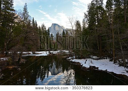 Half Dome And Surrounding Woods Reflected In Merced River In Yosemite National Park, California Unde
